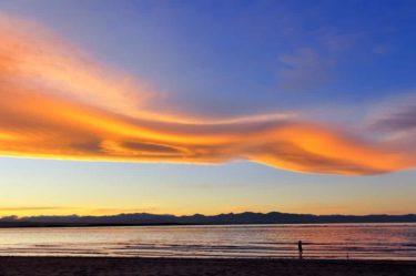 Anglerin unter UFO-Wolken, Tasmanisches Meer, Südinsel, Neuseeland