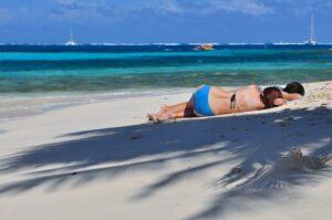 Mädchen relaxen am Strand unter Palmen, Tobago Cays, Grenadinen, Karibik