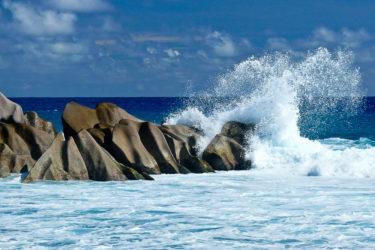 Welle bricht sich an Granitfelsen, La Digue, Seychellen