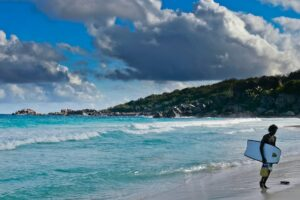 Surfer an der wilden Grande Anse, La Digue, Seychellen