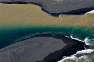 Zweifarbiger Fluss mündet ins Meer, Südküste, Island