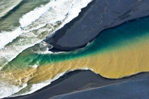 Zweifarbiger Fluss mündet in Atlantik, Luftbild, Island
