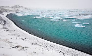 Gletschersee Jökulsarlon mit Eisbergen und verschneitem Ufer am Vatnajökull, Island